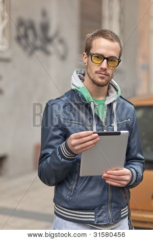 Man on street with tablet