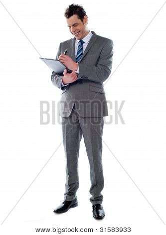 Successful Businessman Writing Notes On Clipboard