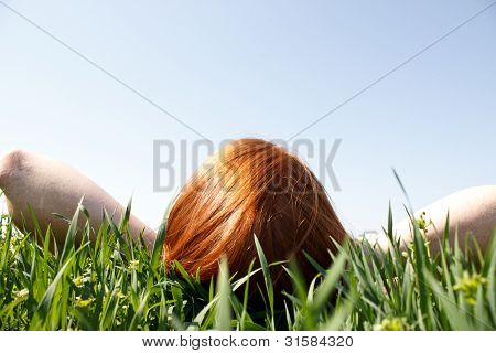 Red Haired Woman Laying In Grass Looking Up