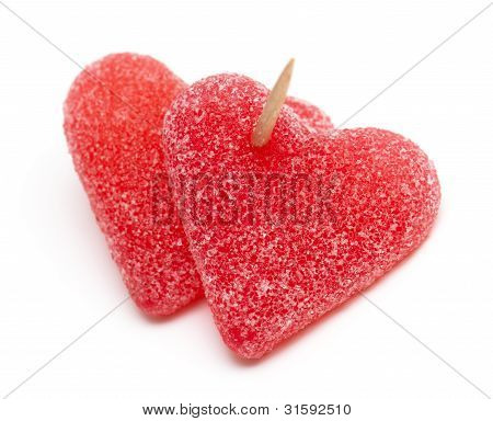 Two Heart-shaped Candies Atached To Each Other With A Toothpick