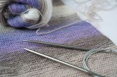 Tools For Needlework: Knitting Fabric, Tangle Of Thread Of Multicolored Yarn, Knitting Needles. Purp poster