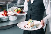 Waiter Serving In Motion On Duty In Restaurant. The Waiter Carries Dishes. poster