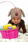 picture of craw  - Baby girl wearing hat with rabbit ears crawing to a basket with colorful Easter eggs  - JPG