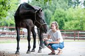 Black Horse Gazing Away Close To Her Owner - Young Teenage Girl At Ranch After Training. Vibrant Mul poster