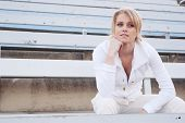 stock photo of bleachers  - young attractive female athlete sitting in the bleachers - JPG