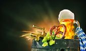 Oktoberfest background with beer stein, beer tap, pretzel, wheat and hops on a barrel poster