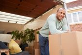 Portrait Of Man Unloading Furniture From Removal Truck Outside New Home On Moving Day poster