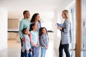 Female Realtor Showing Family Interested In Buying Around House poster