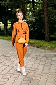 A full length portrait of a stylish pretty fashionable girl walking in the park. Summer casual fashi poster