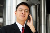 picture of handphone  - Young asian executive talking on a handphone dressed in suit - JPG