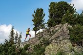 Male Runner Running On A Mountain Trail. Athlete Runs In The Mountains Among The Rocks. Man In A Yel poster