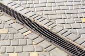 Iron Lattice Drainage On A Pavement Walkway, Close Up Of An Industrial Drainage System. poster