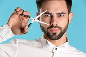 Young Hairstylist Holding Professional Scissors On Color Background, Closeup poster