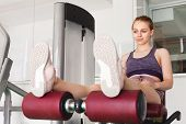 Young Beautiful Blond Sporty Girl Relaxes After A Leg Extension Exercising In A Gym poster