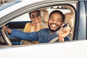 Visiting Car Dealership. Afro Couple Showing Car Key, Looking At Camera And Smiling, Sitting In New  poster