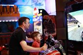 Father And Son Playing Motorbike Simulator In Amusement Center poster
