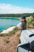 Woman Checking With Map On The Suv Car Hood Lake With Blue Water On Background Copy Space Point On D poster