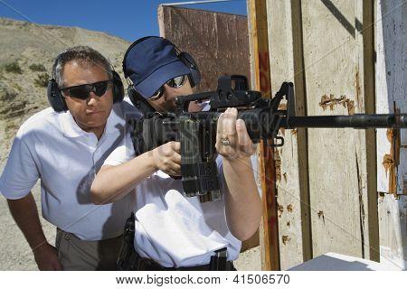 Instructor assisting woman aiming with gun at firing range