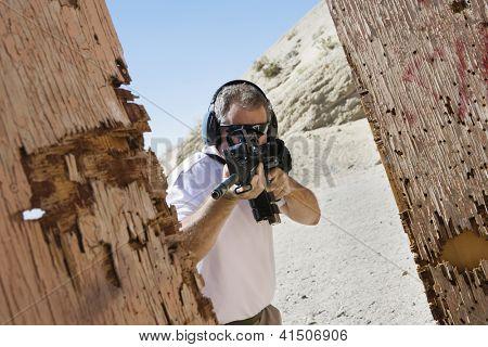 Mature man aiming with gun at combat training