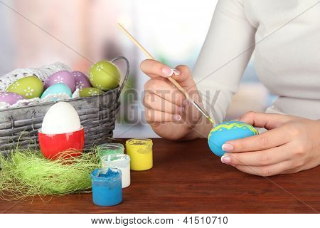 Young woman painting Easter eggs, on bright background