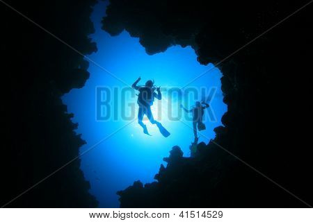 Couple of Scuba Divers descend into an underwater cavern