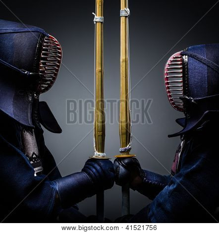 Two kendo fighters opposite each other with bokuto. Japanese martial art of sword fighting