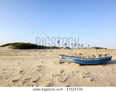 Blue fishing boat in the sand dunes of Jericoacoara, Brazil