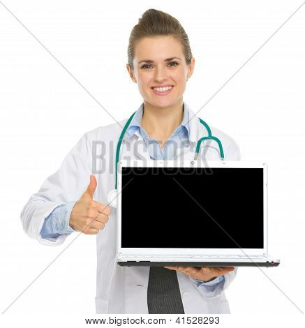 Smiling Medical Doctor Woman Showing Laptop And Thumbs Up