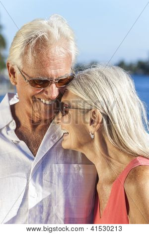 Happy senior man and woman romantic couple laughing together next to tropical sea or river with bright clear blue sky