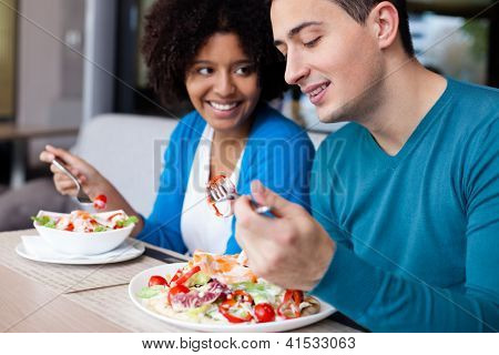 Lovely interracial couple having lunch at restaurant