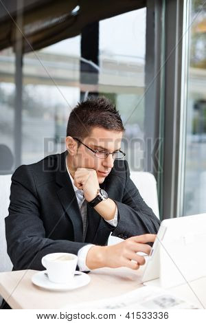 Good-looking manager sitting at desk, using tablet in cafe