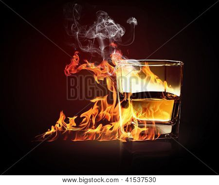 Image of glass of burning yellow absinthe