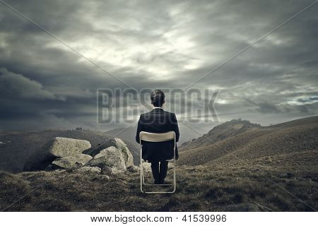 Businessman sitting on a white chair in front of a mountains wasteland