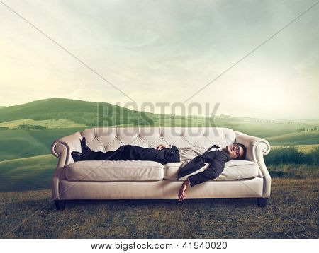 Man lying on a white sofa in a large field