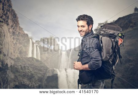 Young man with a travel backpack near a waterfall in Morocco
