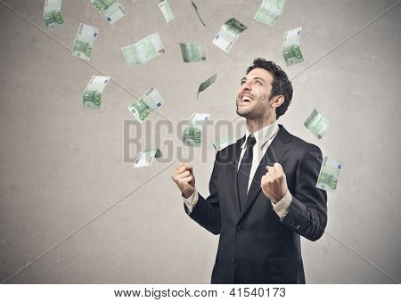Businessman rejoicing for his success with hundred-euro banknotes flying in the air