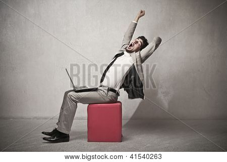 Businessman sitting with a laptop is stretching