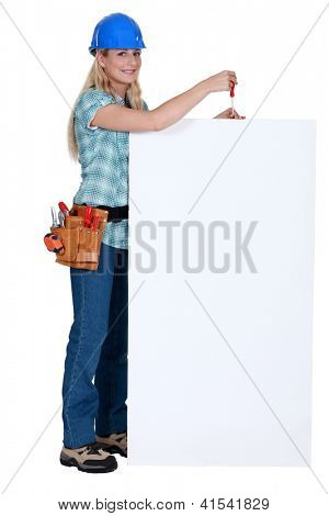 Tradeswoman holding a screwdriver over a blank sign