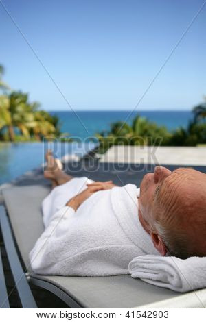 Elderly man relaxing poolside