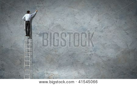businessman standing on ladder drawing diagrams and graphs