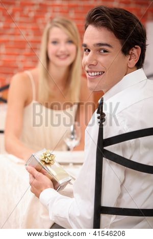 young man giving a present to his girlfriend at restaurant