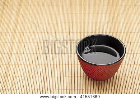 Japanese cup of tea on a bamboo mat - a traditional cast iron red hobnail design with black enamel inside
