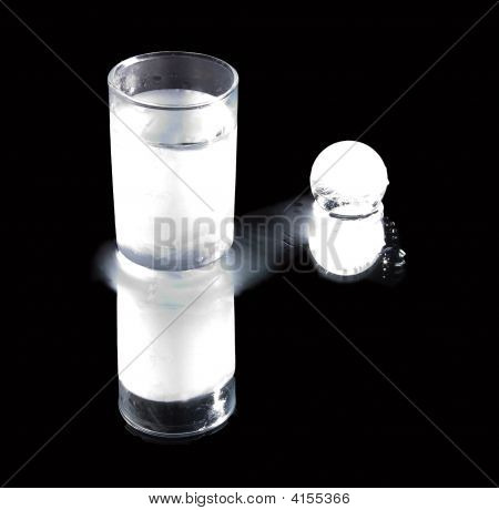 The Frozen Glass With Vodka And Ice Ball On A Mirror Table