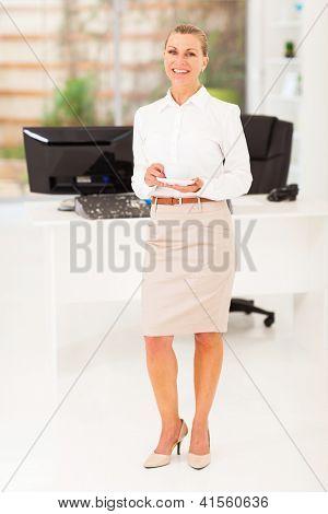 senior businesswoman drinking coffee in office