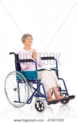 elderly woman sitting on wheelchair and praying isolated on white