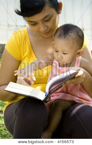 Mother Read Book and Babysit Baby