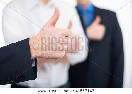 Businessmen gesturing thumbs up