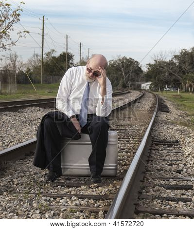 Jobless Business Man Sits On Suitcase On Railroad Train Tracks Holding His Head