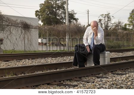 Jobless Senior Businessman Sits On Suitcase On Railroad Train Tracks Tired And Worried