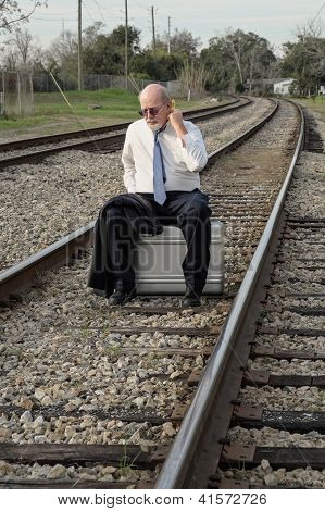Tired Jobless Senior Businessman Sits On Suitcase On Railroad Train Tracks